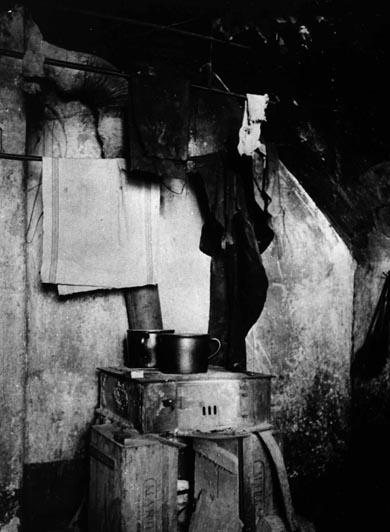 Trotz Arbeit konnten sich im Kaiserreich viele Menschen nur Wohnungen leisten, die nicht mehr als ein Notbehelf waren. Hier eine Innenaufnahme einer Wohnstätte mit Wäsche und einem provisorischen Ofen um 1914. Rechteinhaber nicht ermittelbar.